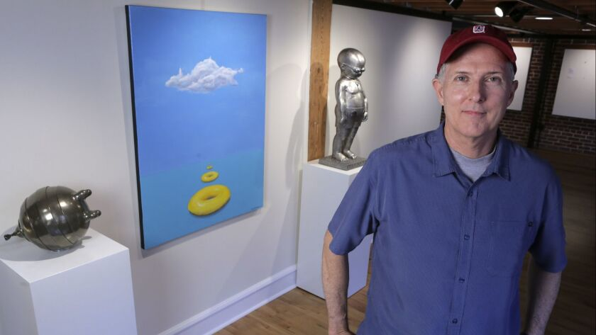 Artist Richard Becker is pictured with some of his works at Sparks Gallery in downtown San Diego whe