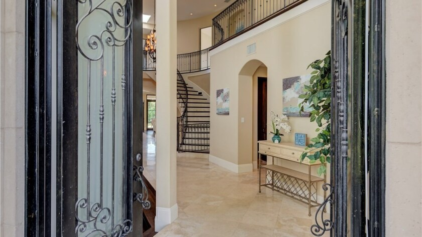 A sweeping staircase with wrought-iron railings sits off the entry great room.