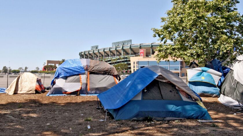 Homeless people live in tents on the Santa Ana River bike trail encampment next to Angel Stadium of