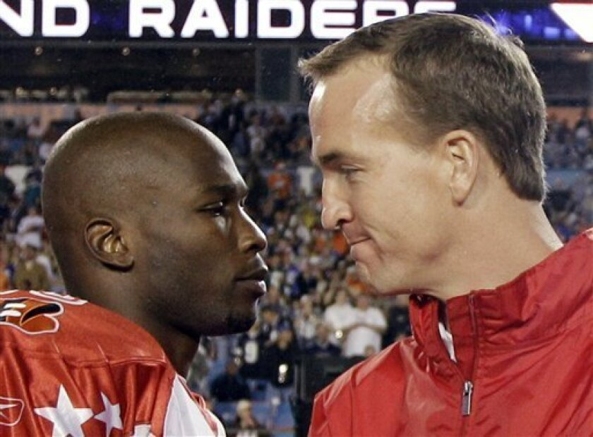 Indianapolis Colts quarterback Peyton Manning talks to Cincinnati Bengals wide receiver Chad Ochocinco, left, on the sidelines before during the NFL football Pro Bowl Sunday, Jan. 31, 2010, in Miami. (AP Photo/David J. Phillip)