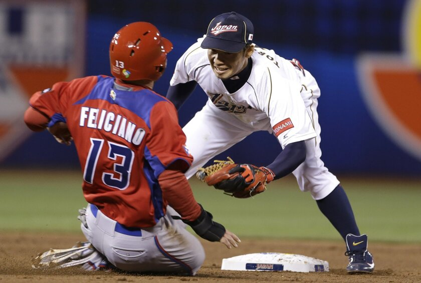 Japan's Takashi Toritani, right, waits to tag out Puerto Rico's Jesus Feliciano trying to steal second base during the fifth inning of a semifinal game of the World Baseball Classic in San Francisco, Sunday, March 17, 2013.