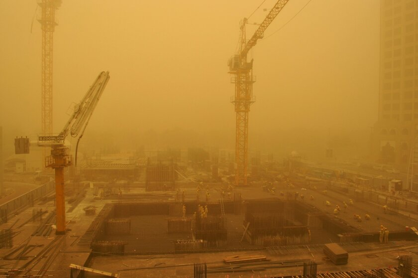 Migrant laborers work on a construction site during a sandstorm in Dubai, United Arab Emirates, Thursday, April 2, 2015. A major sandstorm has whipped into the Mideast's commercial hub of Dubai and other Gulf cities, reducing visibility, forcing flight diversions and making breathing outside more difficult. (AP Photo/Adam Schreck)