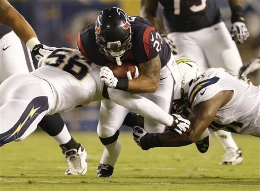 Houston Texans running back Arian Foster drives between San Diego Chargers inside linebacker Donald Butler, left, and defensive end Kendall Reyes during the first half of an NFL football game Monday, Sept. 9, 2013, in San Diego. (AP Photo/Gregory Bull)