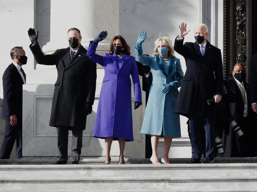 Douglas Emhoff in a black coat, Kamala Harris in purple, Jill Biden in blue and Joe Biden in black wave to the crowd.