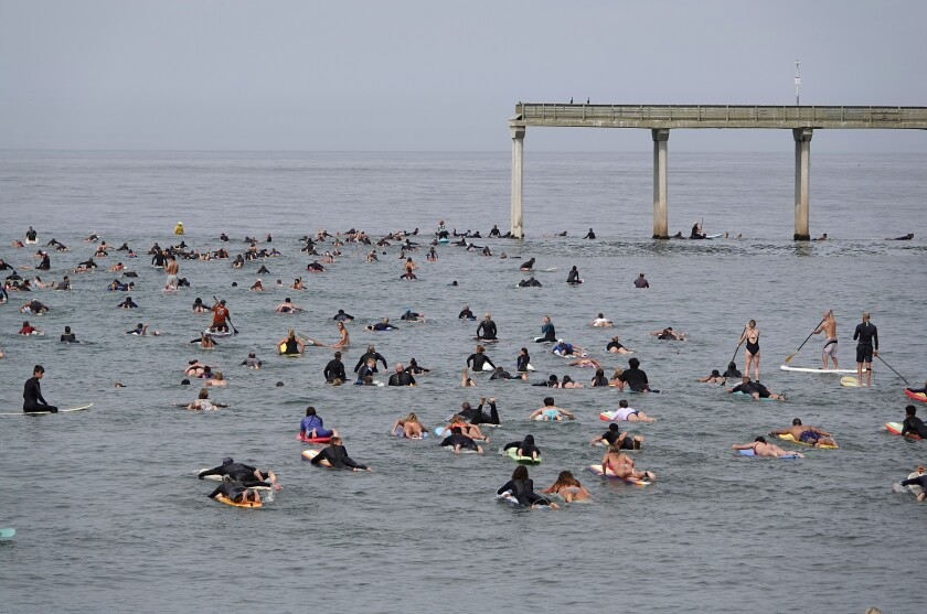 Surfers and paddleboarders paddle around the end of the Ocean Beach pier