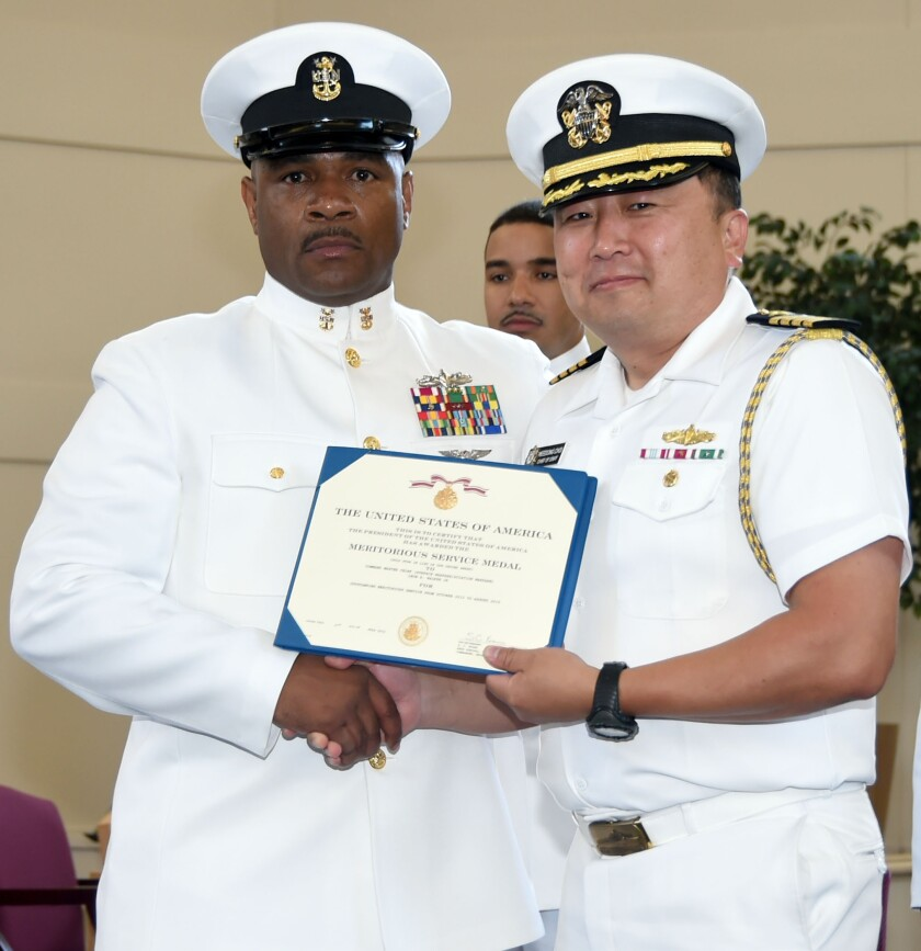 Capt. Heedong Choi (right) presents a Meritorious Service Medal to Command Master Chief Leon R. Walker Jr. at Naval Service Training Command in 2015. Choi was censured April 26 by the Secretary of the Navy for his years-long improper relationship with Leonard Glenn Francis.