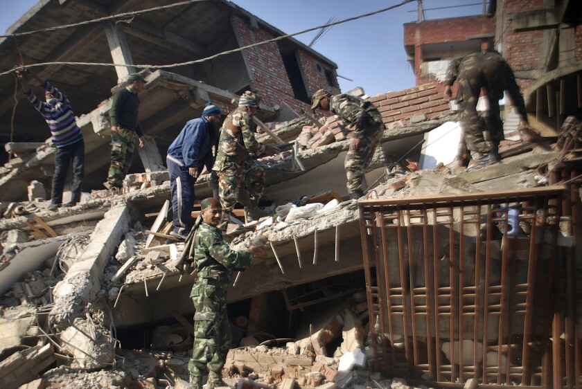 Soldiers and locals remove debris from a damaged building after an earthquake in Imphal, India, on Jan. 4.