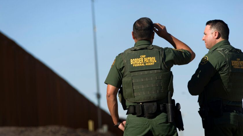 United States Border Patrol agents stand near a section of the recently renovated US-Mexico border wall, in Calexico, California, USA, on 26 October 2018.