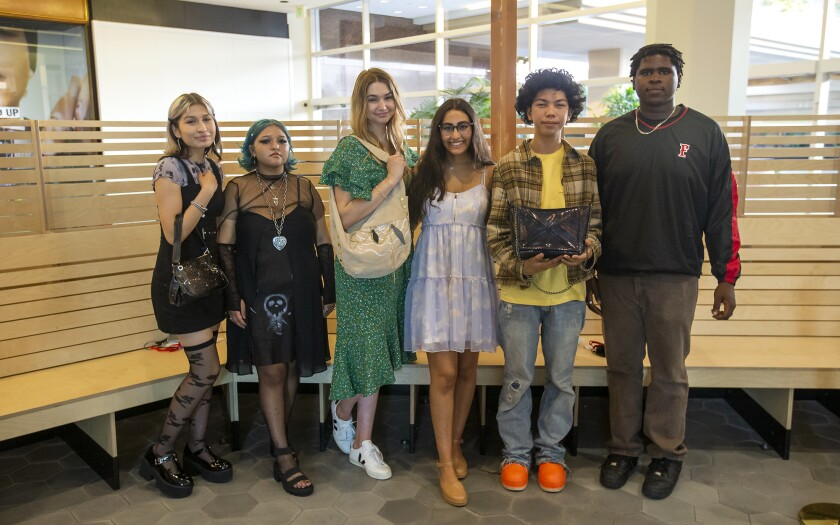 Young fashion designers from Orange County schools pose with handbags they recycled at a fashion show Thursday.