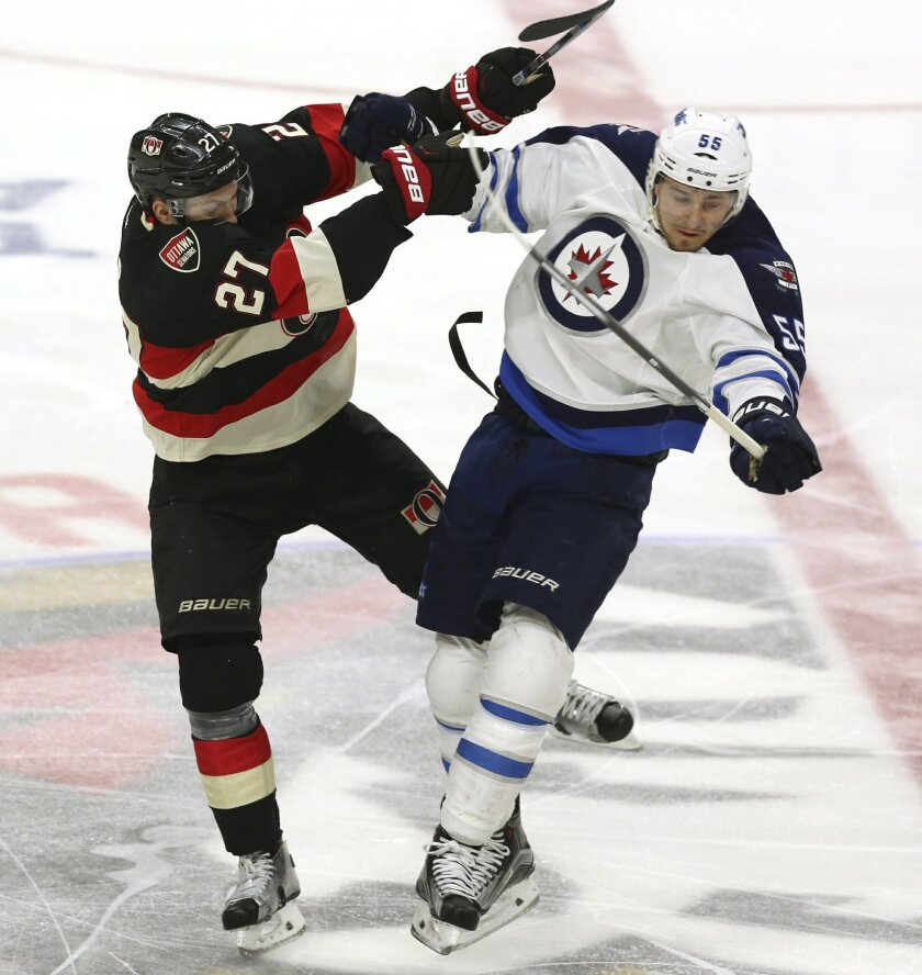 Winnipeg Jets' Mark Scheifele (55) collides with Ottawa Senators' Curtis Lazar during the second period of an NHL hockey game Thursday, Nov. 5, 2015, in Ottawa, Ontario. (Fred Chartrand/The Canadian Press via AP)