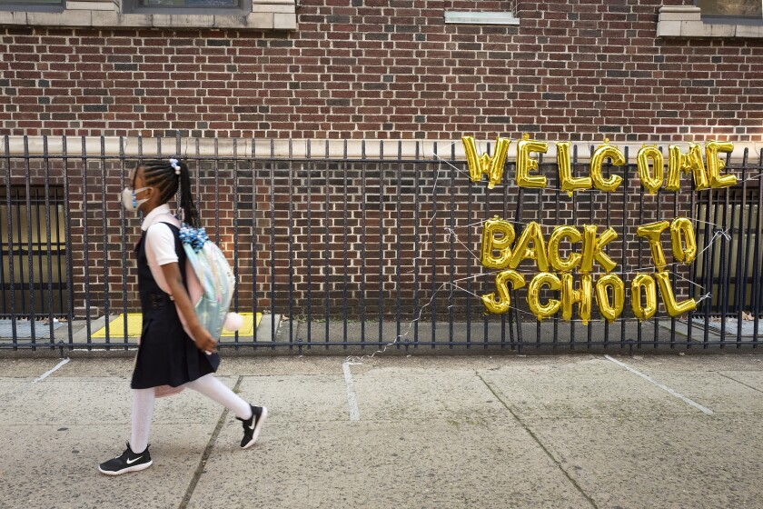 """A girl in uniform passes a """"Welcome Back to School"""" sign as she arrives for the first day of class"""