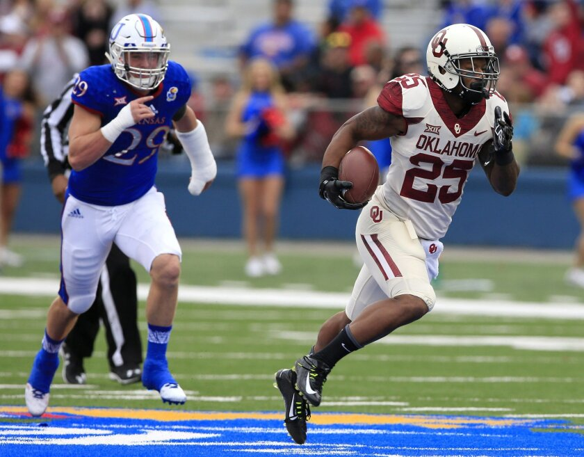 Oklahoma running back Joe Mixon (25) runs away from Kansas linebacker Joe Dineen Jr. (29) for a touchdown during the first half of an NCAA college football game in Lawrence, Kan., Saturday, Oct. 31, 2015. (AP Photo/Orlin Wagner)
