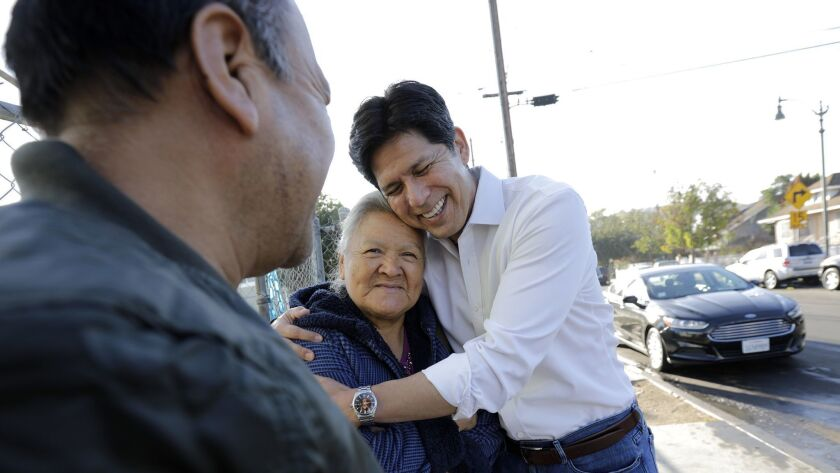 California state Sen. Kevin de León, right, a candidate in the U.S. Senate election in California, chats with Leobarda Loyola, 76, and her brother Juan Loyola, 60, left, on his way to La Abeja restaurant in Los Angeles.