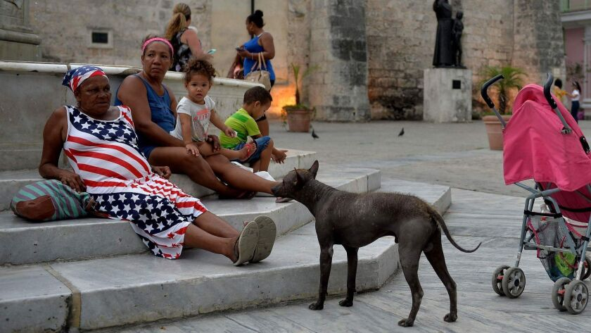A woman wearing a dress with a U.S. flag design rests at a square in Havana on May 6.