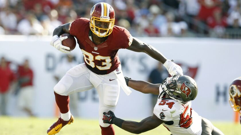 Tight end Fred Davis, then with the Washington Redskins, fends off Tampa Bay Buccaneers linebacker Lavonte David during a game in September 2012. Davis is trying to revive his football career in the XFL.