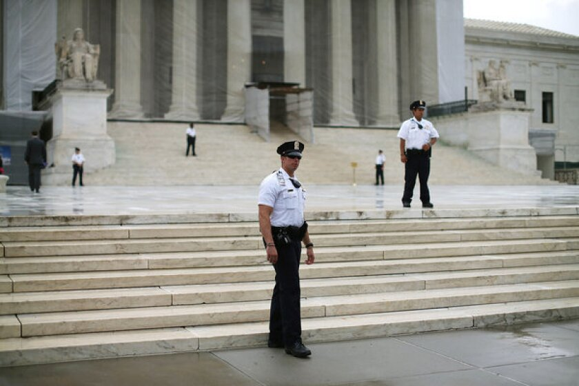 Police stand guard in front of the U.S. Supreme Court building.