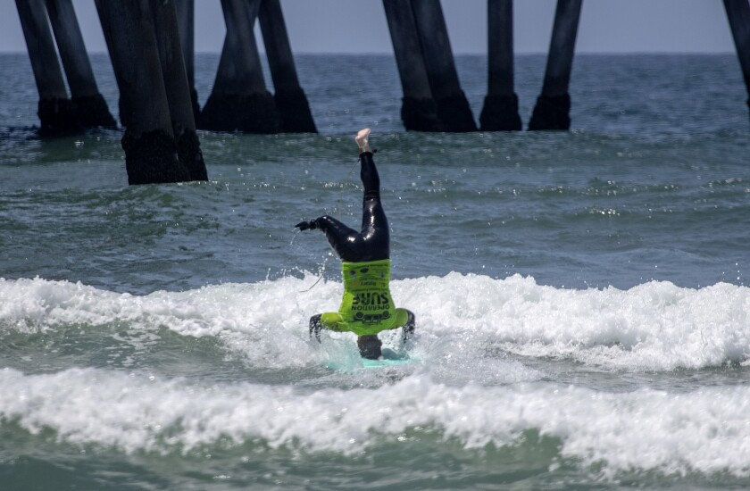U.S. Army veteran Stephen Peterson, who lost his leg to an IED in Afghanistan in 2011, does a headstand while surfing in Huntington Beach.