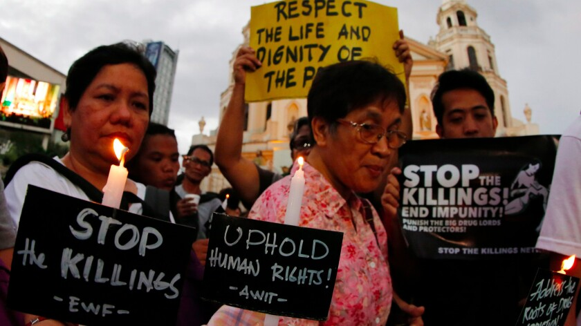 Filipino human rights advocates hold candles and placards during a protest condemning recent extrajudicial killings in front of a church in Manila.