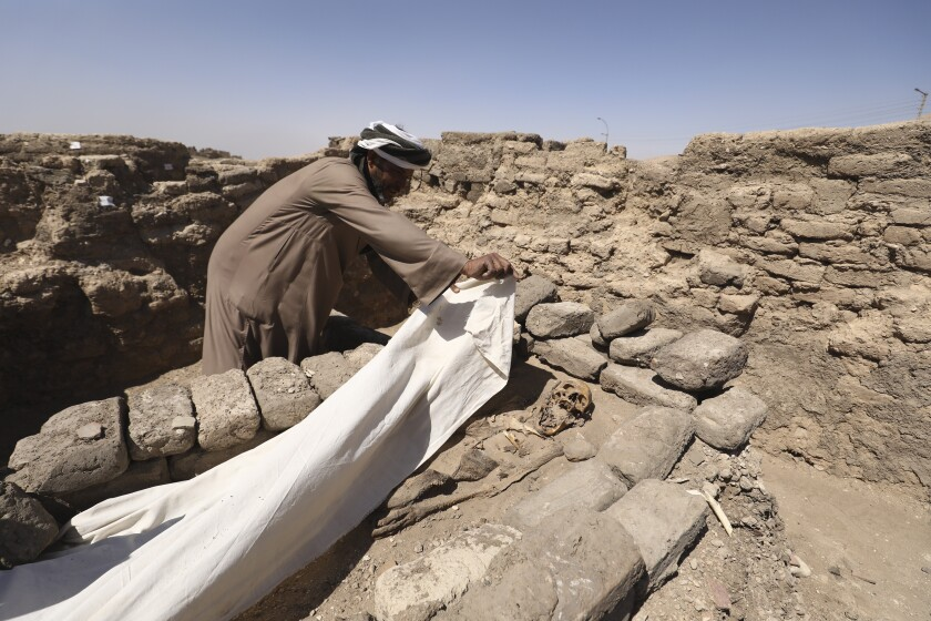 A man cover a skeleton in a 3,000-year-old lost city in Luxor province, Egypt, Saturday, April 10, 2021. The newly unearthed city is located between the temple of King Rameses III and the colossi of Amenhotep III on the west bank of the Nile in Luxor. The city continued to be used by Amenhotep III's grandson Tutankhamun, and then his successor King Ay. (AP Photo/Mohamed Elshahed)