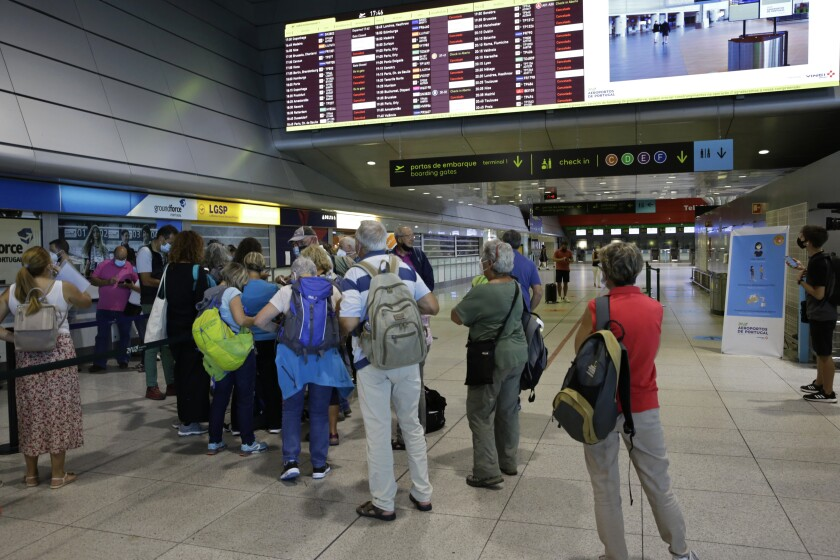 Passengers queue at the counter of Groundforce, a ground handling company at Lisbon airport, beneath a screen showing departing flights Saturday, July 17, 2021. A strike by ground handling workers at Portugal's airports forced the cancellation of over 200 flights on Saturday. The walkouts over wage conditions are scheduled to last through Sunday. (AP Photo/Armando Franca)