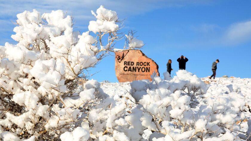 Tourists take pictures at Red Rock Canyon, which was blanketed with snow on Monday.