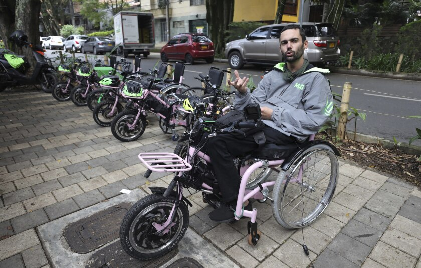 Martin Londoño, owner of MATT, an electric wheelchair tour company talks during an interview in Medellin, Colombia, Wednesday, Nov. 18, 2020. Londoño, 31, started to work on the hand-cycles four years ago in a bid to improve his own mobility. He lost the use of his legs after breaking his spinal chord in a traffic accident at age 18. (AP Photo/Fernando Vergara)
