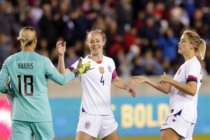 U.S. goalkeeper Ashlyn Harris (18), defender Becky Sauerbrunn (4) and defender Abby Dahlkemper, right, celebrate the team's 8-0 win over Panama in a CONCACAF women's Olympic qualifying soccer match Friday, Jan. 31, 2020, in Houston. (AP Photo/Michael Wyke)