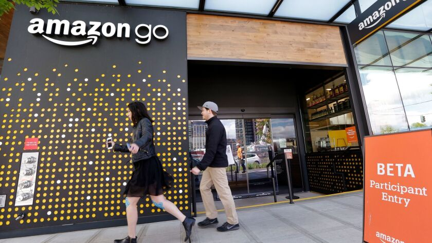 People walk past the Amazon Go store in Seattle.