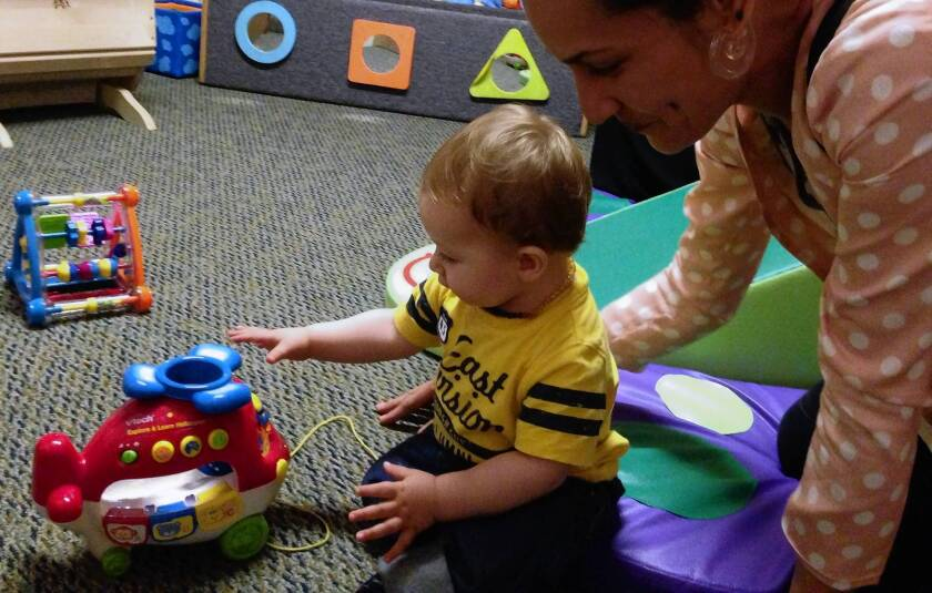 "Single mother Beth Capper plays with her son Ezekiel Goss, 11 months, at the Children's Institute Inc.'s Mid-Wilshire campus. Capper has struggled to pay for diapers. ""There's no way around buying them,"" she said."