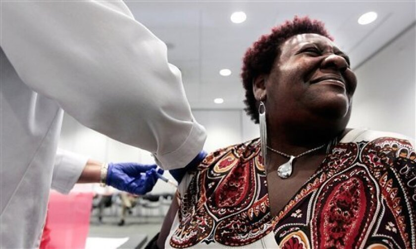FILE - In a Tuesday, Oct. 30, 2012 file photo, Elizabeth Saint Victor winces as she gets a free flu shot from LPN Jean Buck courtesy of Baptist Healthcare in Memphis, Tenn., at the Central Library. Health officials say flu season is off to its earliest start in nearly 10 years _ and it could be a bad one. Officials said Monday, Dec. 3, 2012 that suspected flu cases have jumped in five southern states _ Alabama, Louisiana, Mississippi, Tennessee and Texas. An uptick in flu reports like this usually doesn't occur until after Christmas. (AP Photo/The Commercial Appeal, Jim Weber, File)