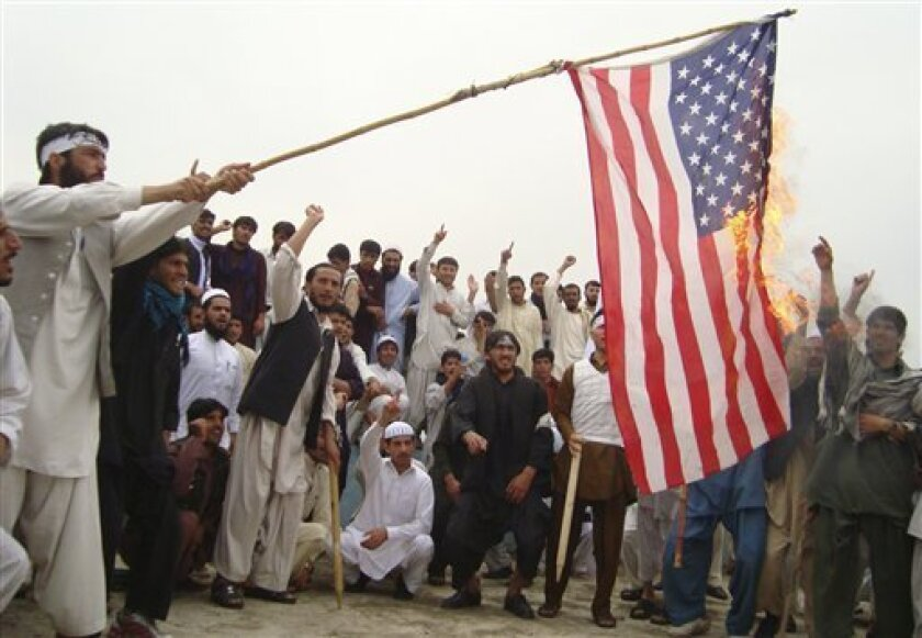 Afghan university students burn the U.S. flag during a demonstration against the burning of the Quran in Khost, Afghanistan, Saturday April 9, 2011. (AP Photo/Nishan Ahingar)