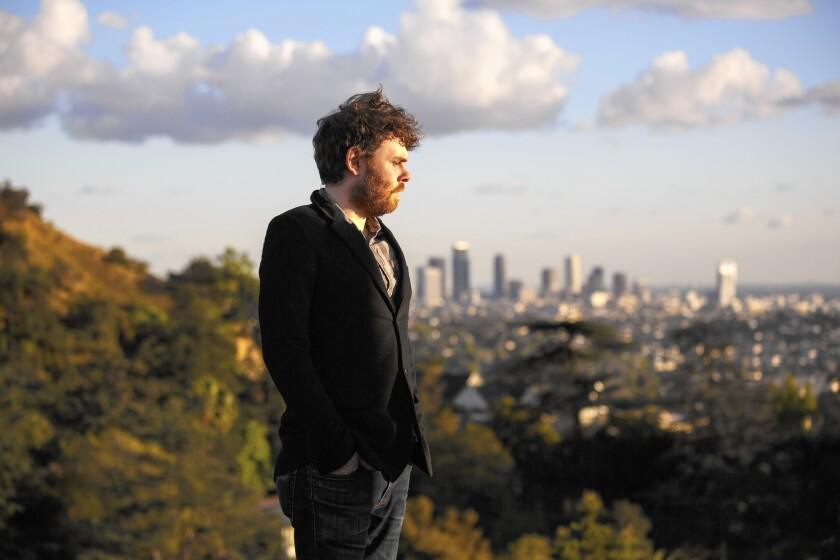 Musician Gabriel Kahane, standing in Los Feliz, with downtown Los Angeles beyond.