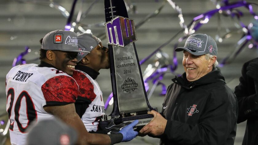 Aztecs Rashaad Penny and Damontae Kazee and head coach Rocky Long lift trophy after beating Wyoming in the Mountain West Championship Game. giving SDSU back-t0-back titles.
