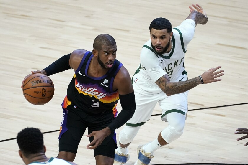 Phoenix Suns guard Chris Paul (3) drives as Milwaukee Bucks guard D.J. Augustin defends during the first half of an NBA basketball game Wednesday, Feb. 10, 2021, in Phoenix. (AP Photo/Matt York)