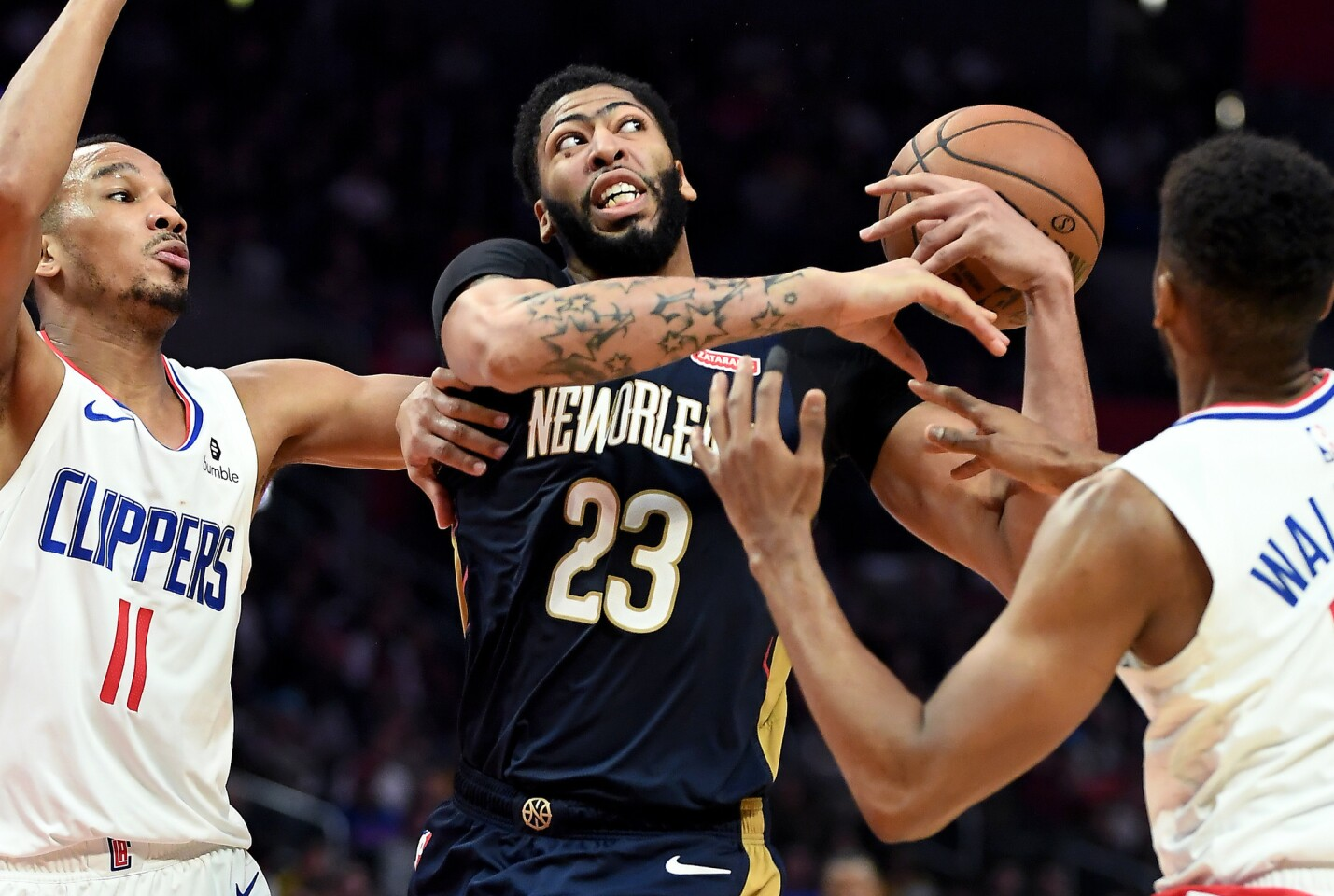 Pelicans Anthony Davis is fouled by Clippers Tyrone Wallace, right, as Avery Bradley helps on defense in the 4th quarter at the Staples Center Monday.