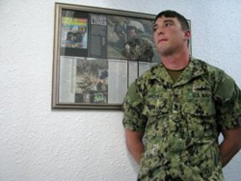 Mass Communications Specialist 2nd Class Derek R. Sanchez in front of the Popular Photography Magazine November 2011 issue he appeared in. Photo/Jeanne McKinney