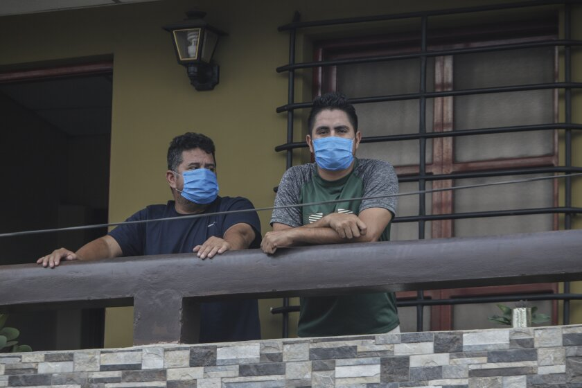 Norman Cardoze Sr., left, and his son Norman Cardoze Jr. pose for a photo from the balcony of their home where they are in quarantine after catching the new coronavirus in Managua, Nicaragua, Wednesday, May 27, 2020. During a May 16 game, manager Norman Cardoze Sr. and coach Carlos Aranda felt sick. Cardoze's son Norman Jr., the team's star slugger, was so weak and achy he didn't play. Within two days all three men were hospitalized, where the Cardozes spent a week and Aranda died. (AP Photo/Alfredo Zuniga)