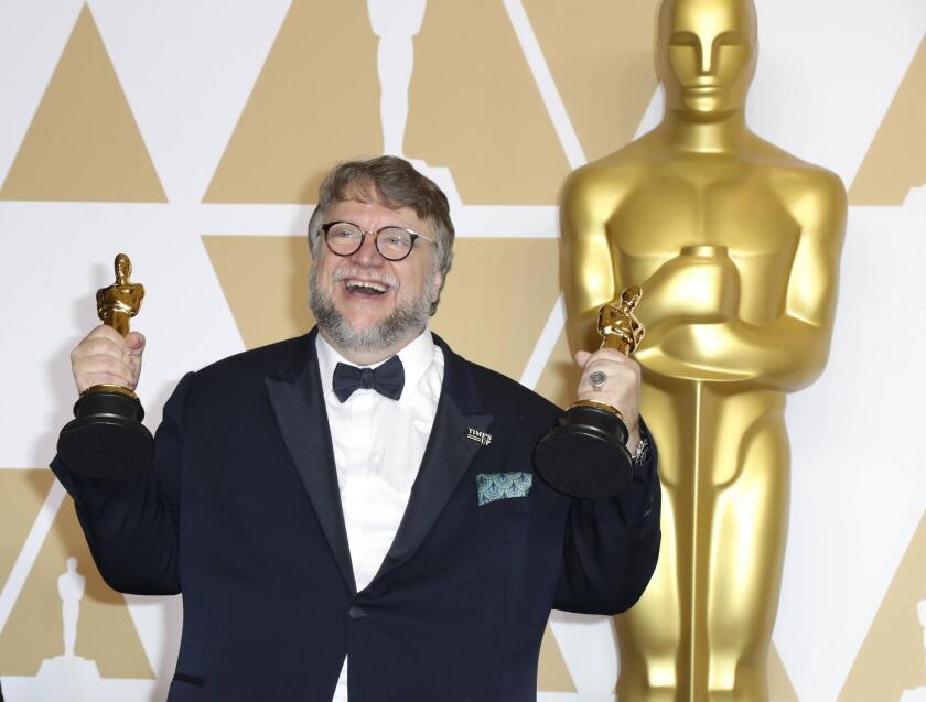 Guillermo del Toro posa con las dos estatuillas que lo consagraron como el cineasta más celebrado en la edición número 90 del Oscar.