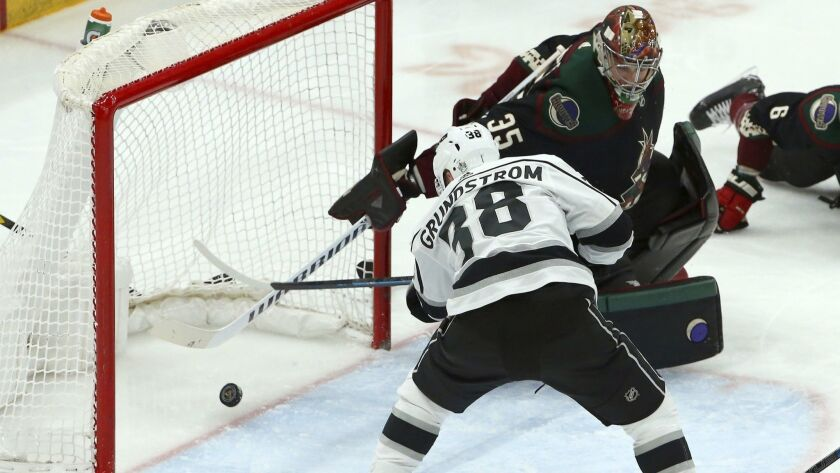 Kings right wing Carl Grundstrom (38) scores a goal against Arizona Coyotes goaltender Darcy Kuemper, top right, during the third period.