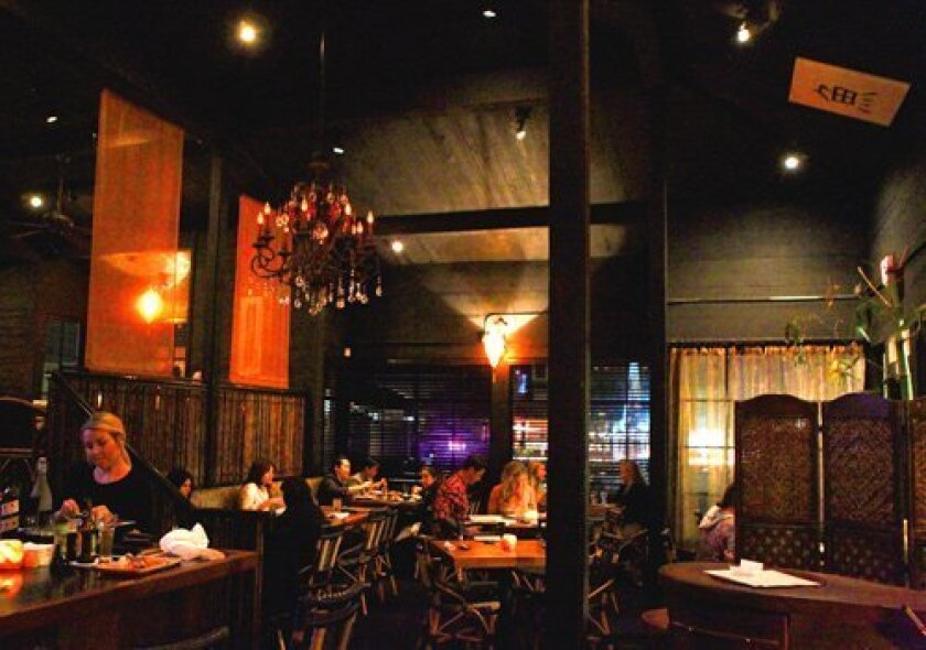 Zenbu Sushi in La Jolla evokes a lounge atmosphere with dim lighting, candles on wooden tables, bamboo accents, Asian-inspired decor, and world-beat music playing in the background. (Photo by Daniel K. Lew)