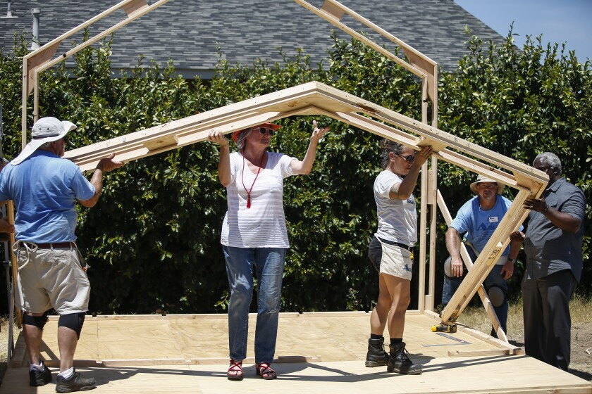 As volunteers Trish Rutter, left, and Denise Lozano support the middle, volunteers move the roof and wall support into place as the cabin begins to take shape on the foundation.