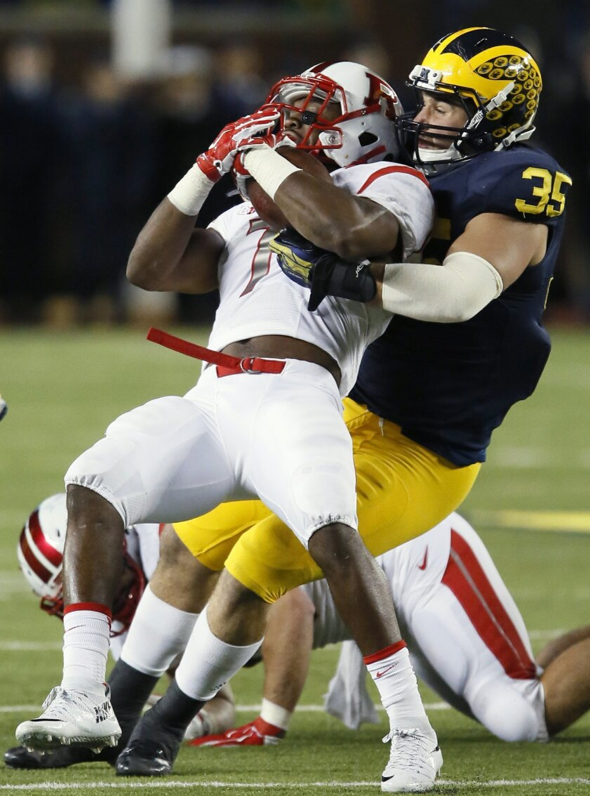 Rutgers' Robert Martin (7) is tackled by Michigan's Joe Bolden (35) during the second half of an NCAA college football game Saturday, Nov. 7, 2015, in Ann Arbor, Mich. Michigan defeated Rutgers 49-16. (AP Photo/Duane Burleson)