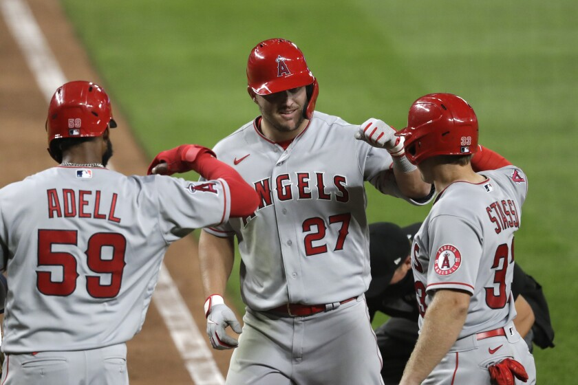 Angels' Mike Trout is met at home by Jo Adell and Max Stassi on his three-run home run against the Seattle Mariners.