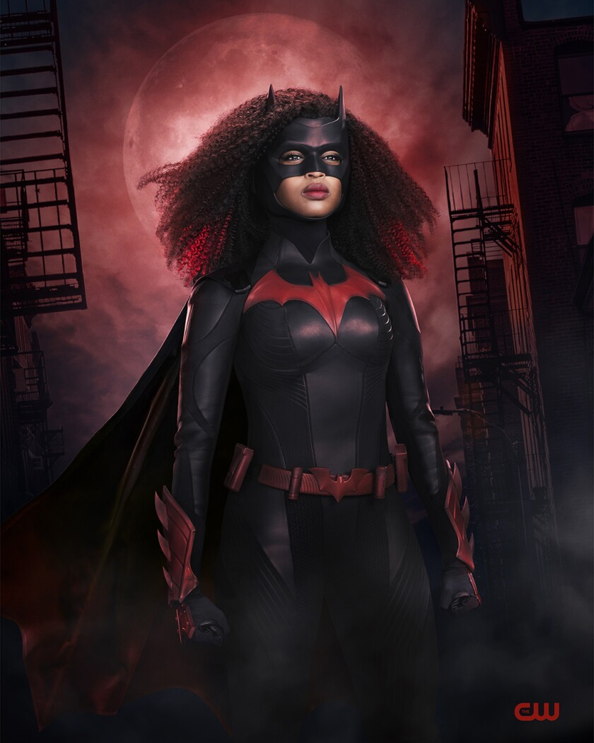 A woman wearing a black bodysuit with a red bat logo, a mask and cape