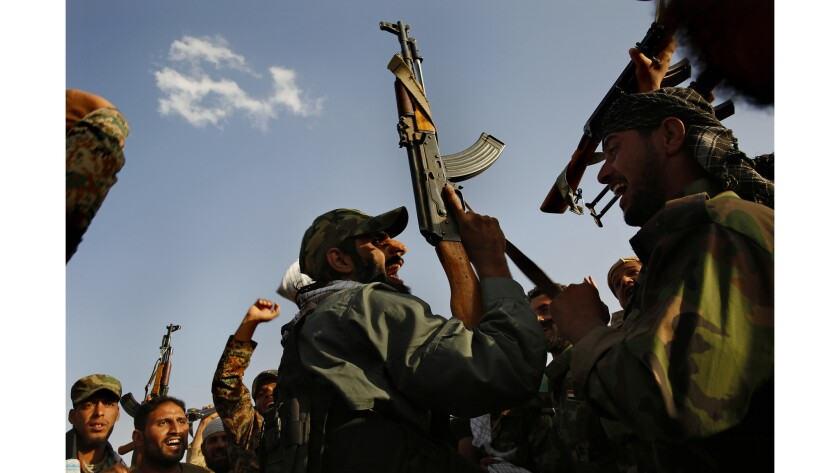 Popular mobilization units chant before going into battle as they fight alongside Iraq army forces.
