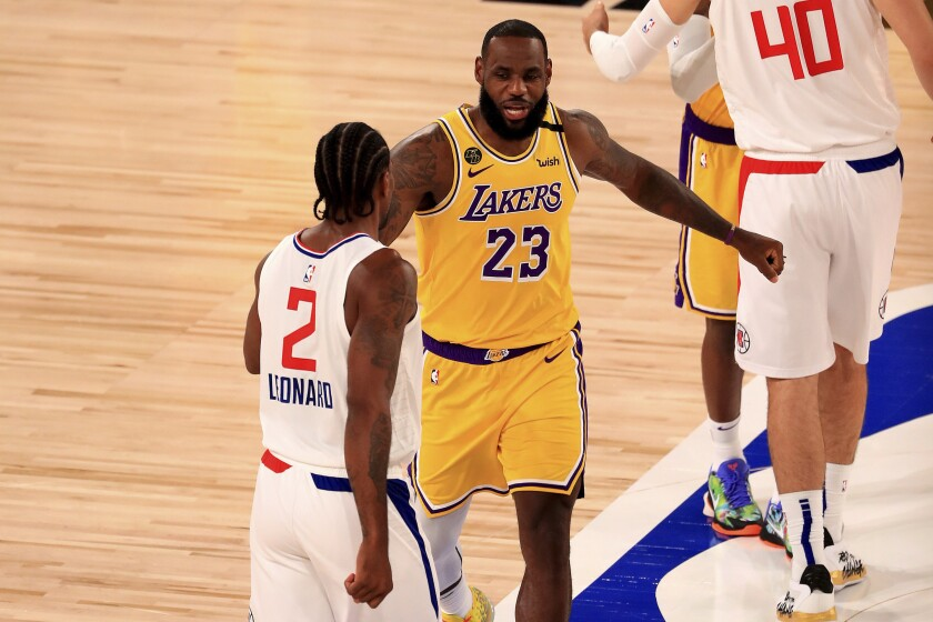 Lakers star LeBron James greets Clippers star Kawhi Leonard before their game last Thursday.