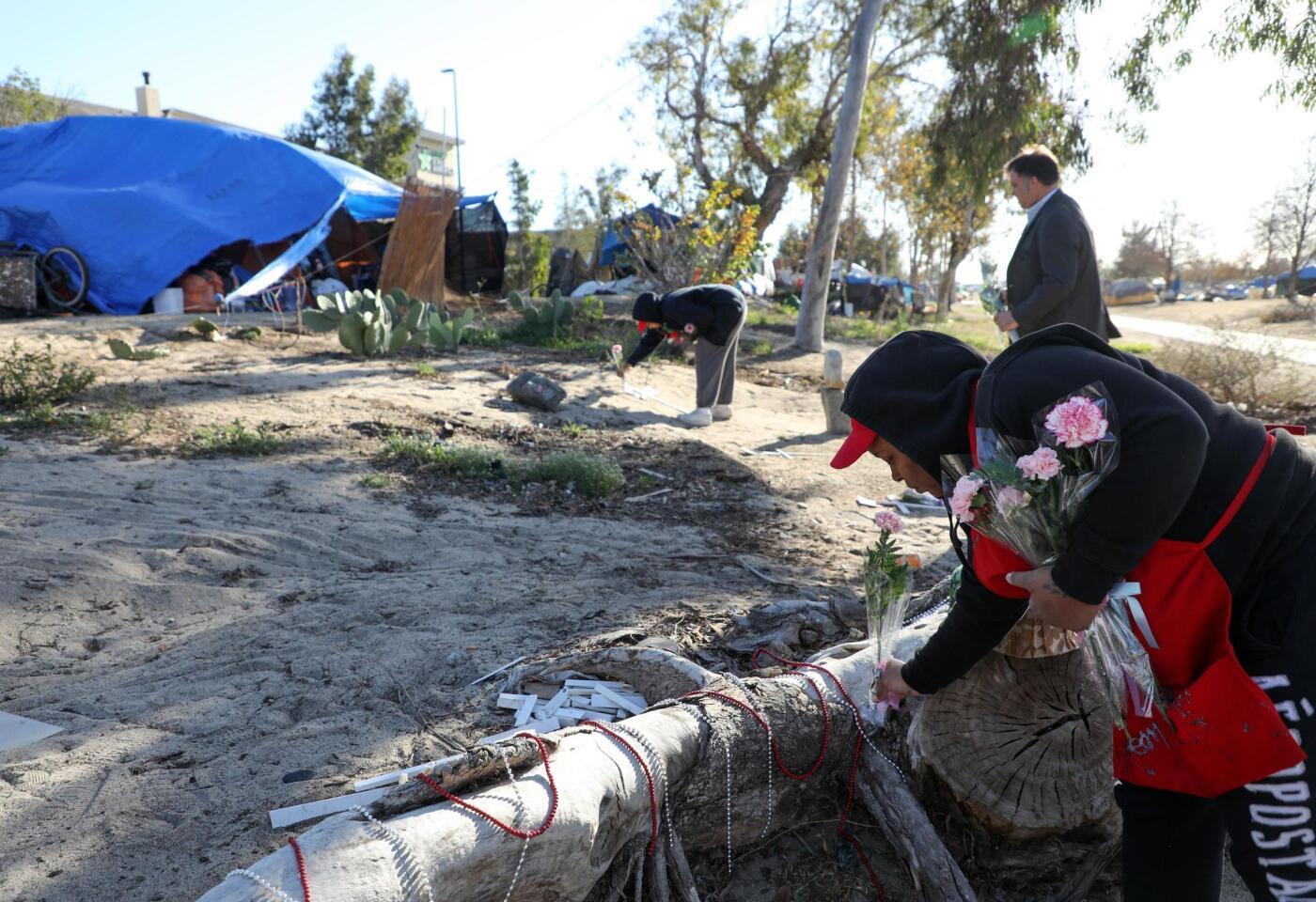 Una mujer deja flores en un campamento junto al lecho del río Santa Ana durante el 'Día de conmemoración a personas sin hogar', en Anaheim, California.