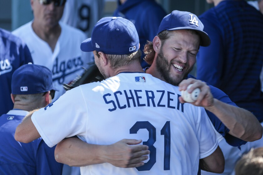 Dodgers starting pitcher Max Scherzer is hugged by teammate Clayton Kershaw in the dugout.