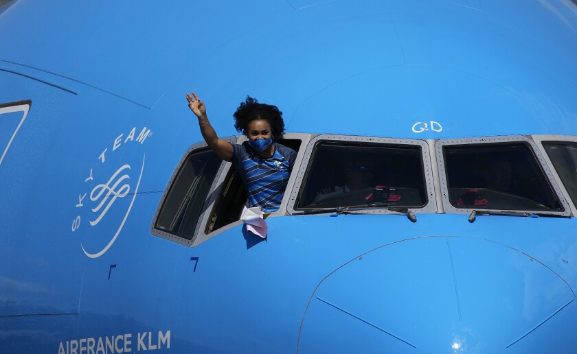 Olympian athlete Neisi Dajomes Barrera, who won the gold in women's weightlifting 76kg at the 2020 Tokyo Olympics, waves from the cockpit of a plane as she arrives to Quito, Ecuador, Wednesday, Aug. 4, 2021. Dajomes Barrera is the first woman from Ecuador to win a gold medal at an Olympics. (AP Photo/Dolores Ochoa)