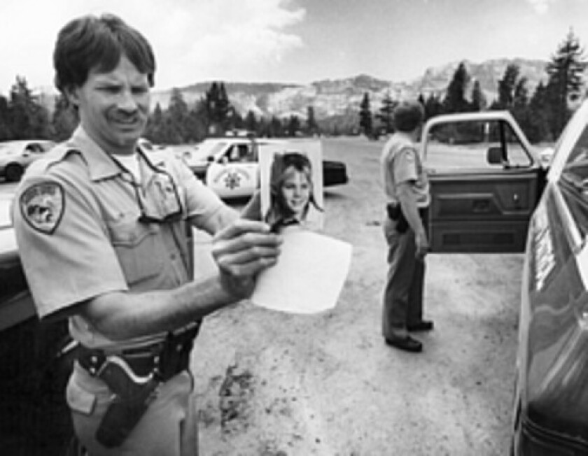 An El Dorado County sheriff's deputy holds a photo of Jaycee Lee Dugard during a search for her shortly after she was kidnapped in 1991.